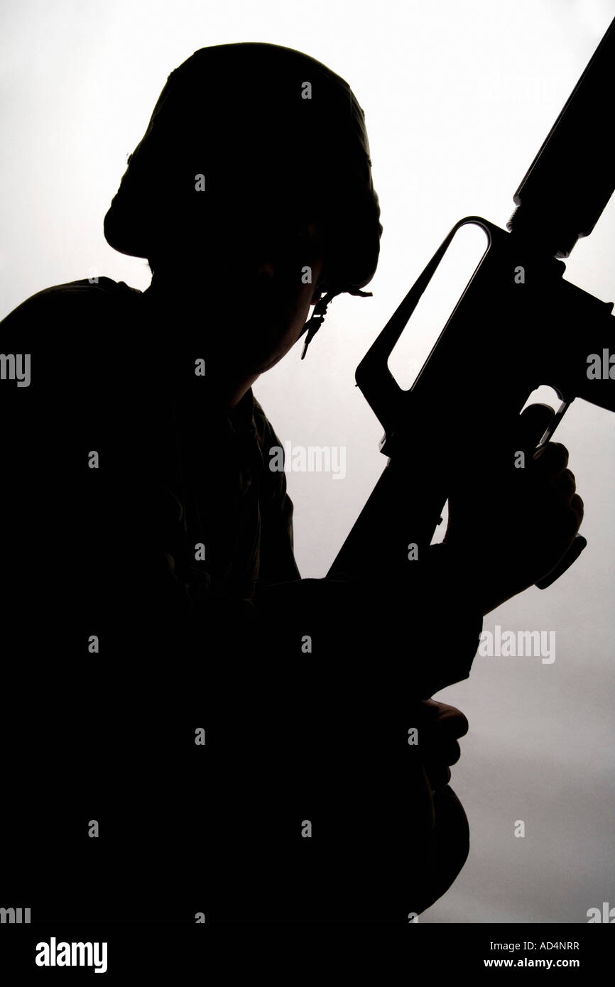 Silhouette of a soldier holding a gun - Stock Image