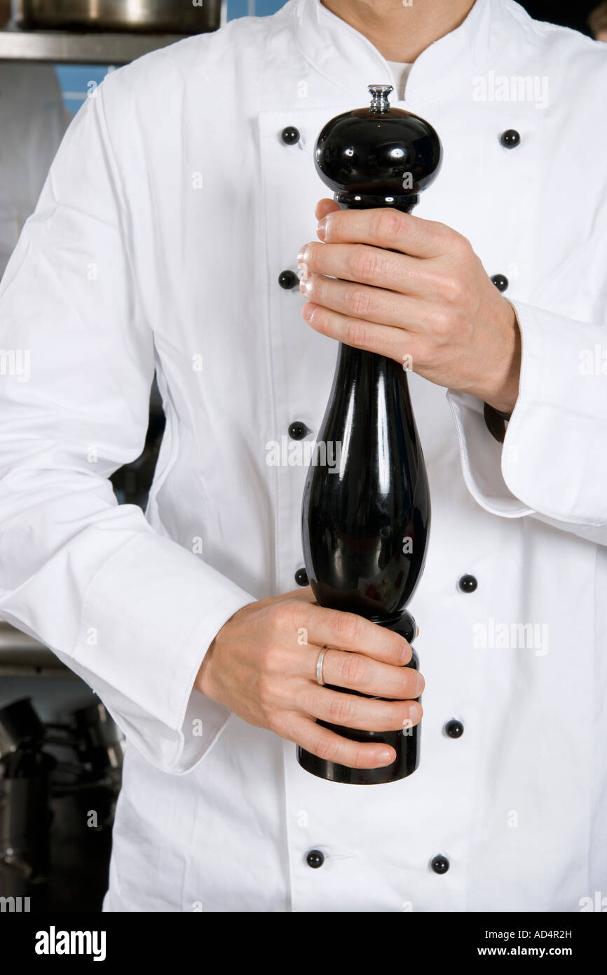 A chef holding a pepper mill - Stock Image