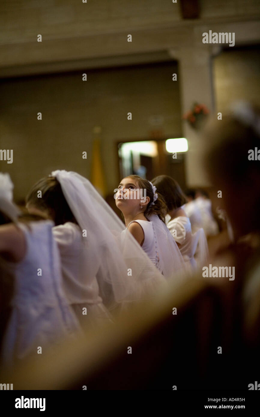 A young girl looking up at her holy communion ceremony - Stock Image