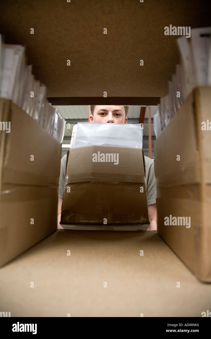 A young man storing a box of paperwork - Stock Image