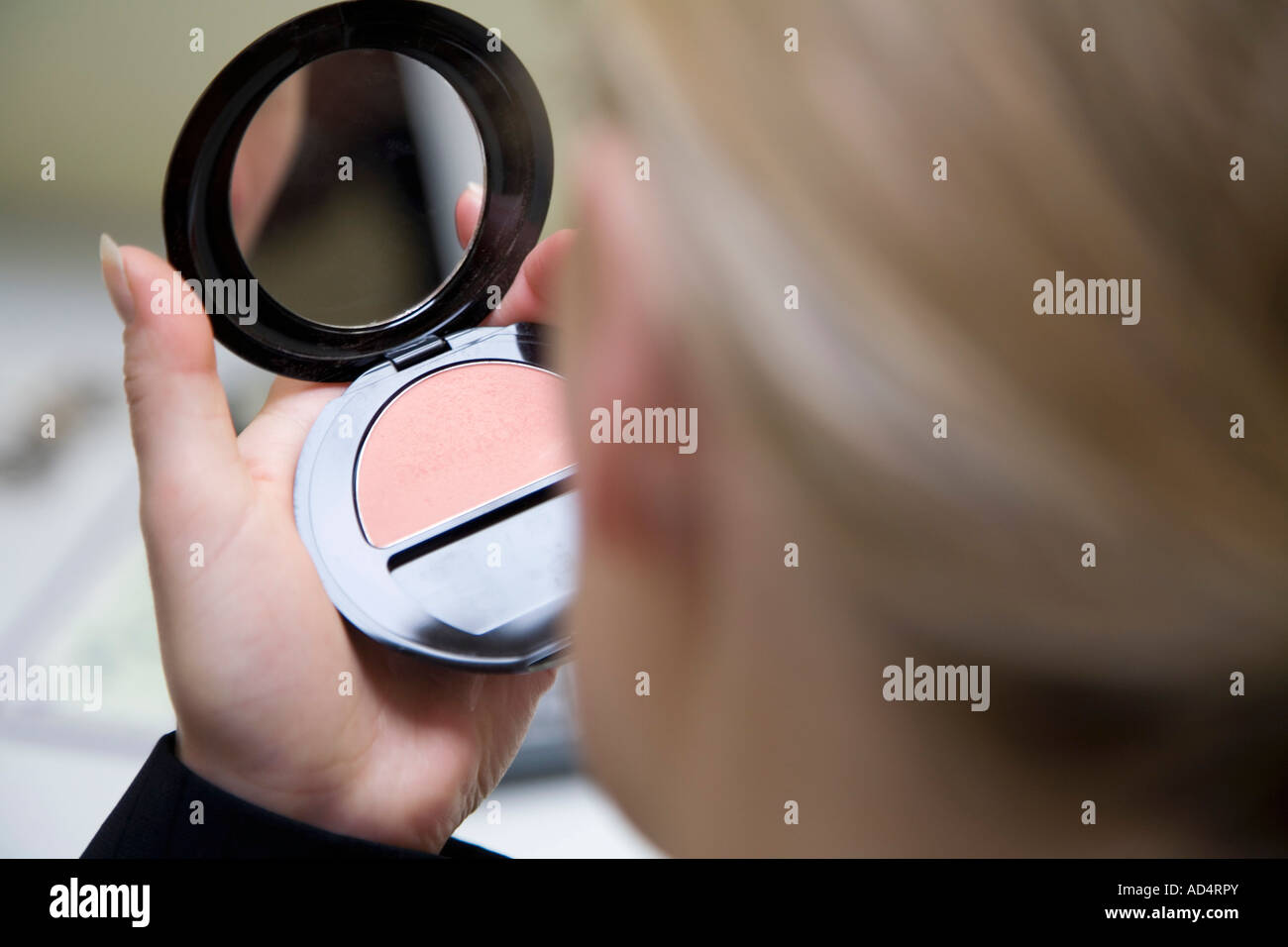 Detail of a woman holding a pressed powder compact - Stock Image
