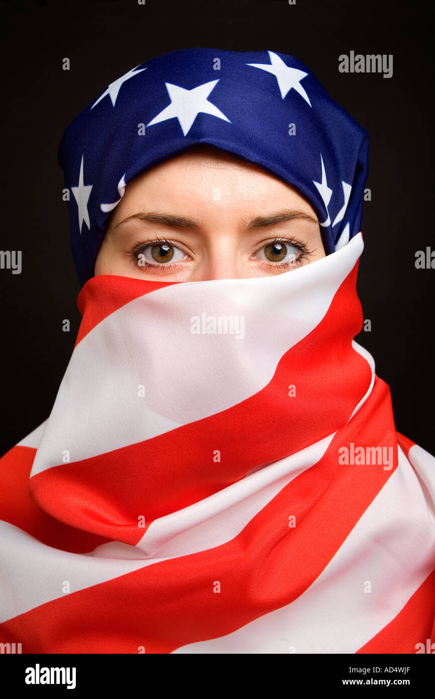 Muslim woman wearing an American USA US  flag as a  hijab burka with a black background - Stock Image