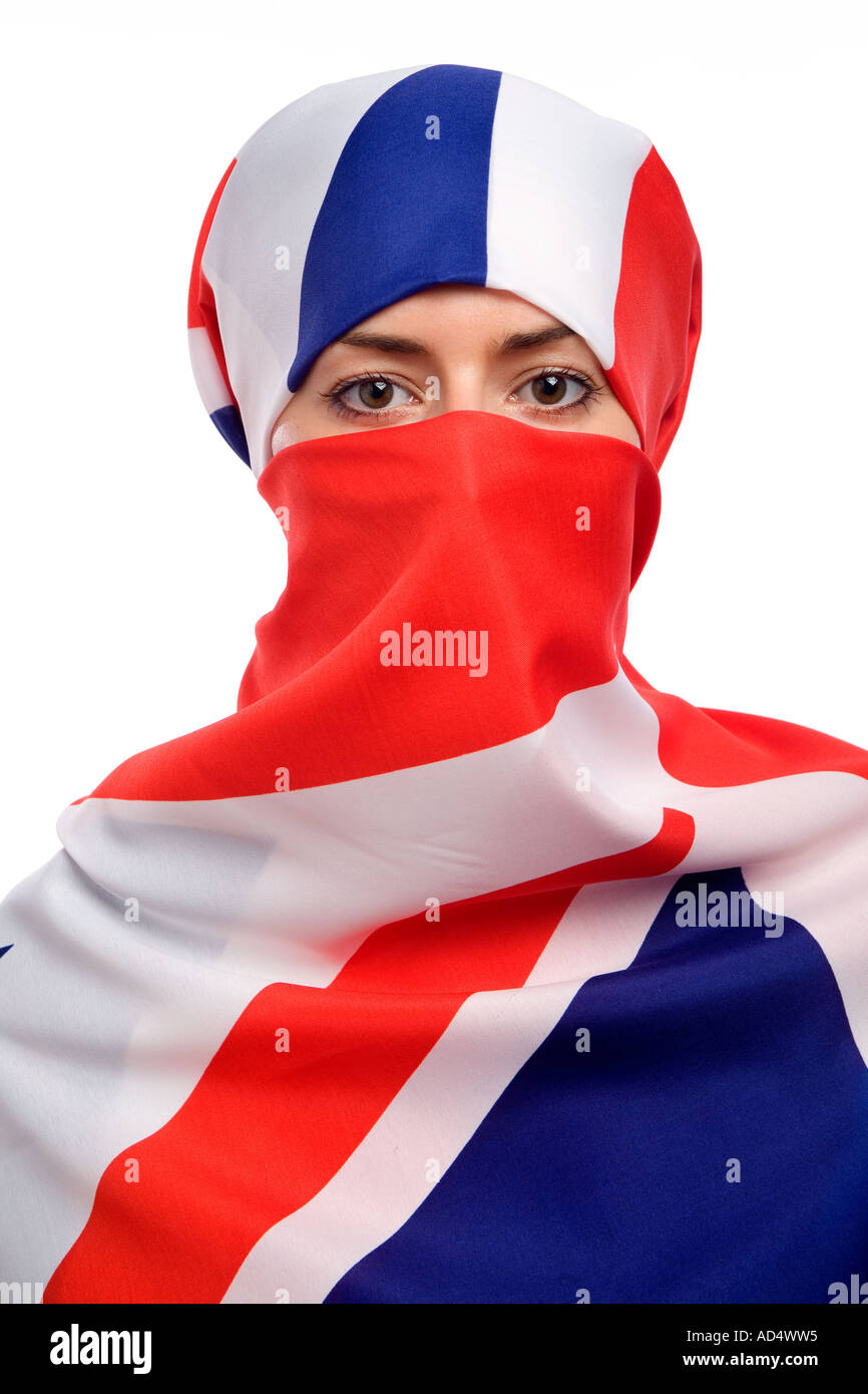 Muslim woman wearing a union jack flag as a  hijab burka with a white background - Stock Image