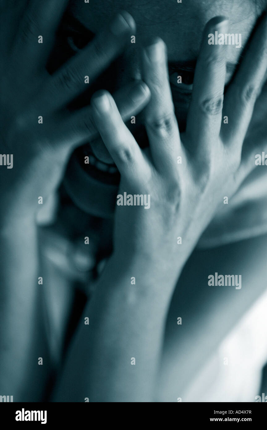 woman peeks maniacally  through the  spread fingers of her hands - Stock Image