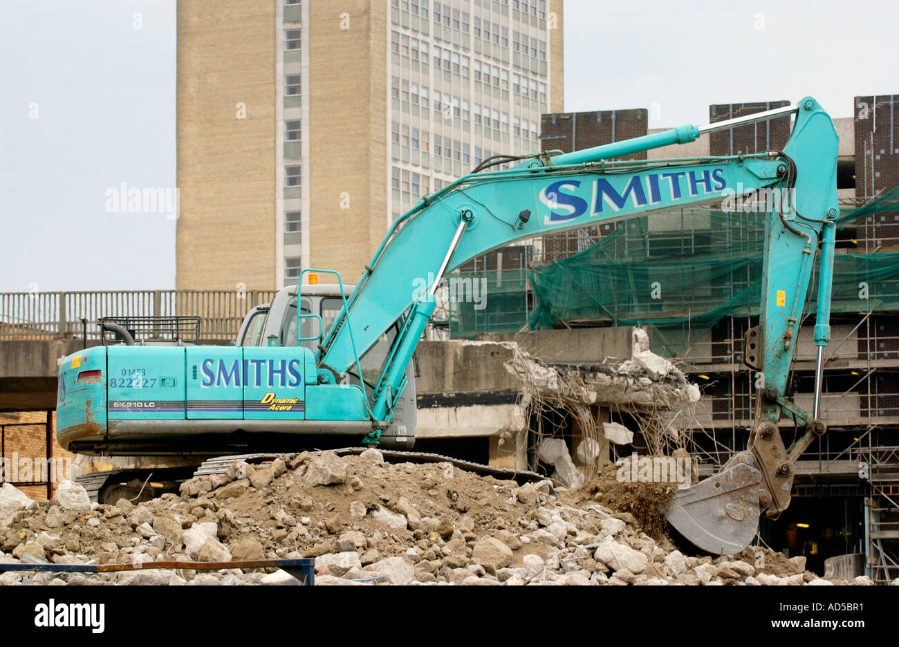 Former car park being demolished by excavator to develop a new shopping centre in Newport Gwent South Wales UK - Stock Image