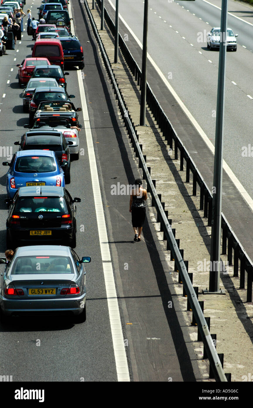Closed motorway due to an accident with bored motorist caught up in a long tailback people pollution climate change - Stock Image
