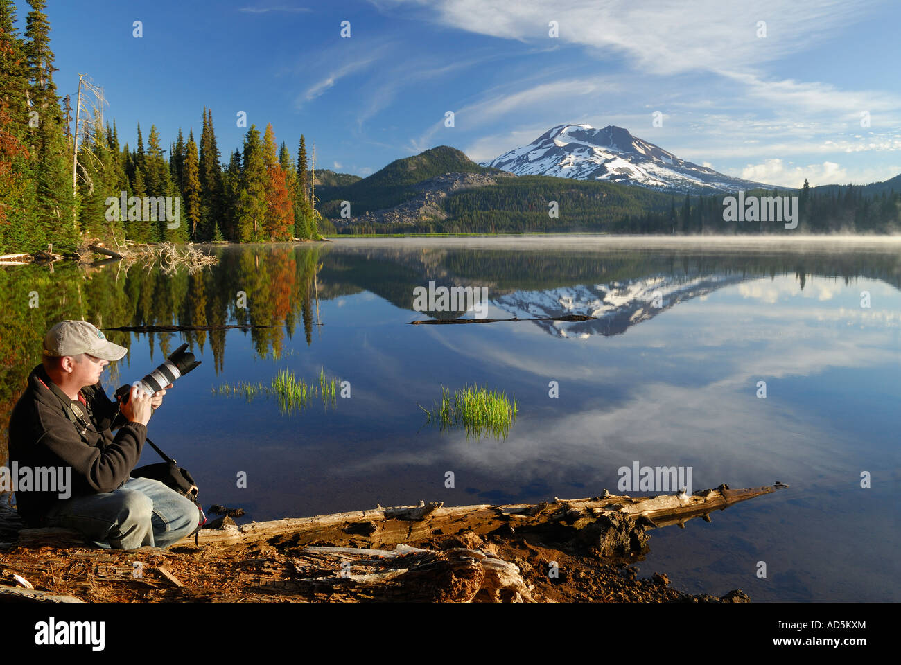 Photographer on shore of calm Sparks Lake with South Sister mountain Deschutes National Forest Bend Oregon - Stock Image