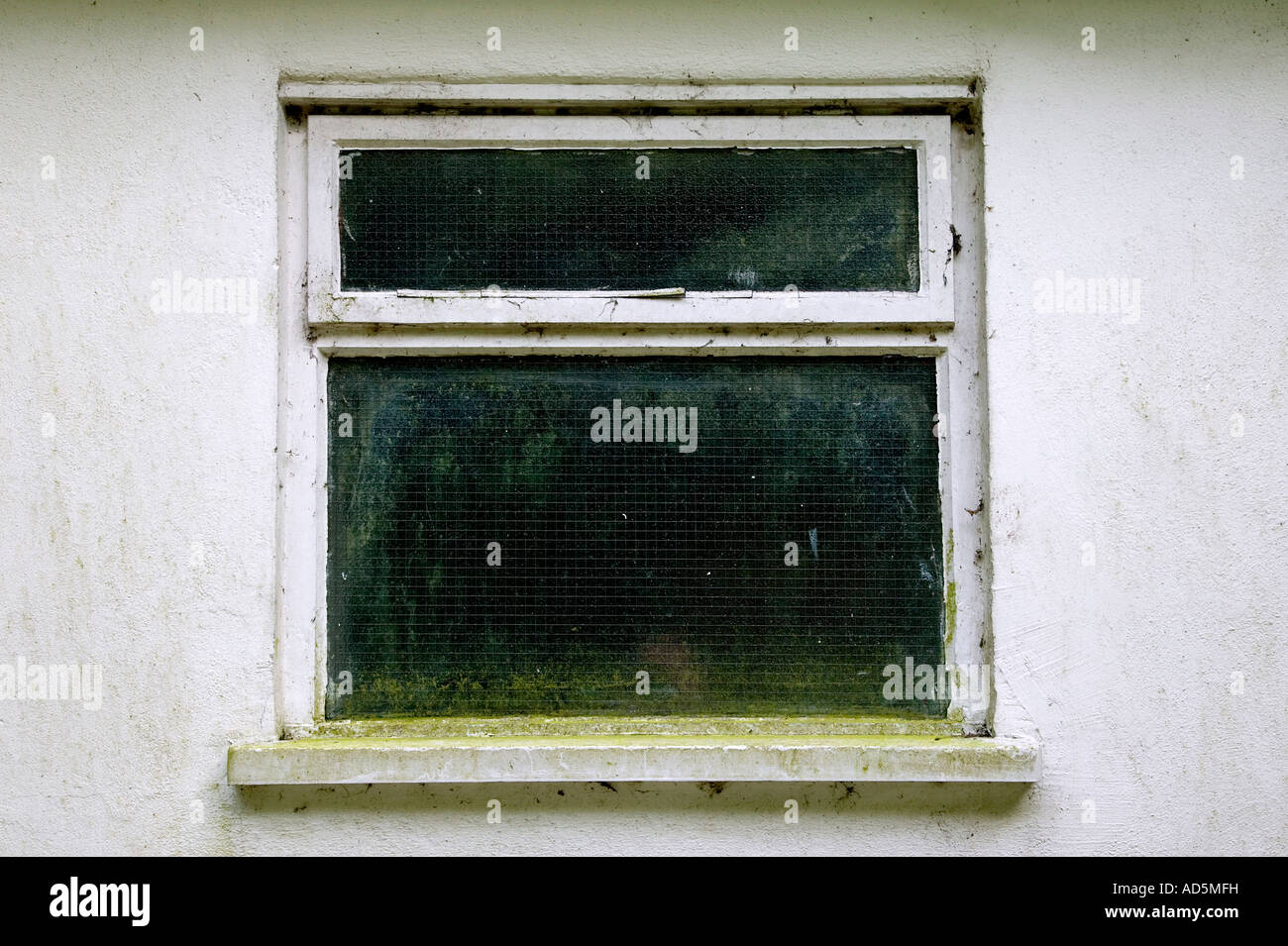 Grungy dirty old window on a white wall - Stock Image