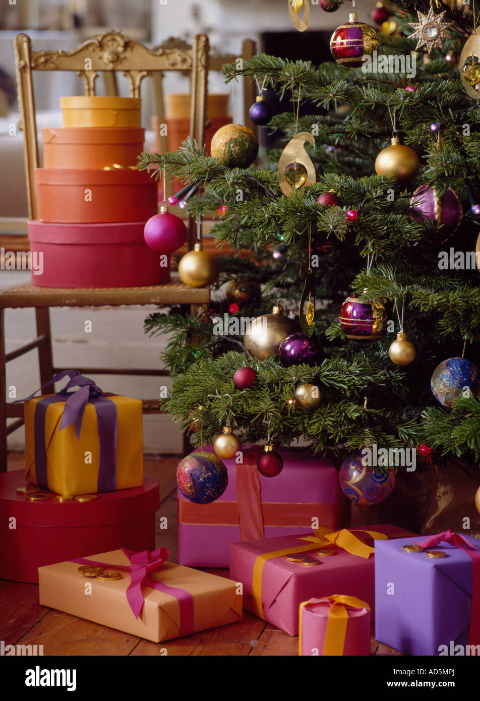 circular pink and oranges plywood boxes on chair beside decorated christmas tree with wrapped christmas presents beneath