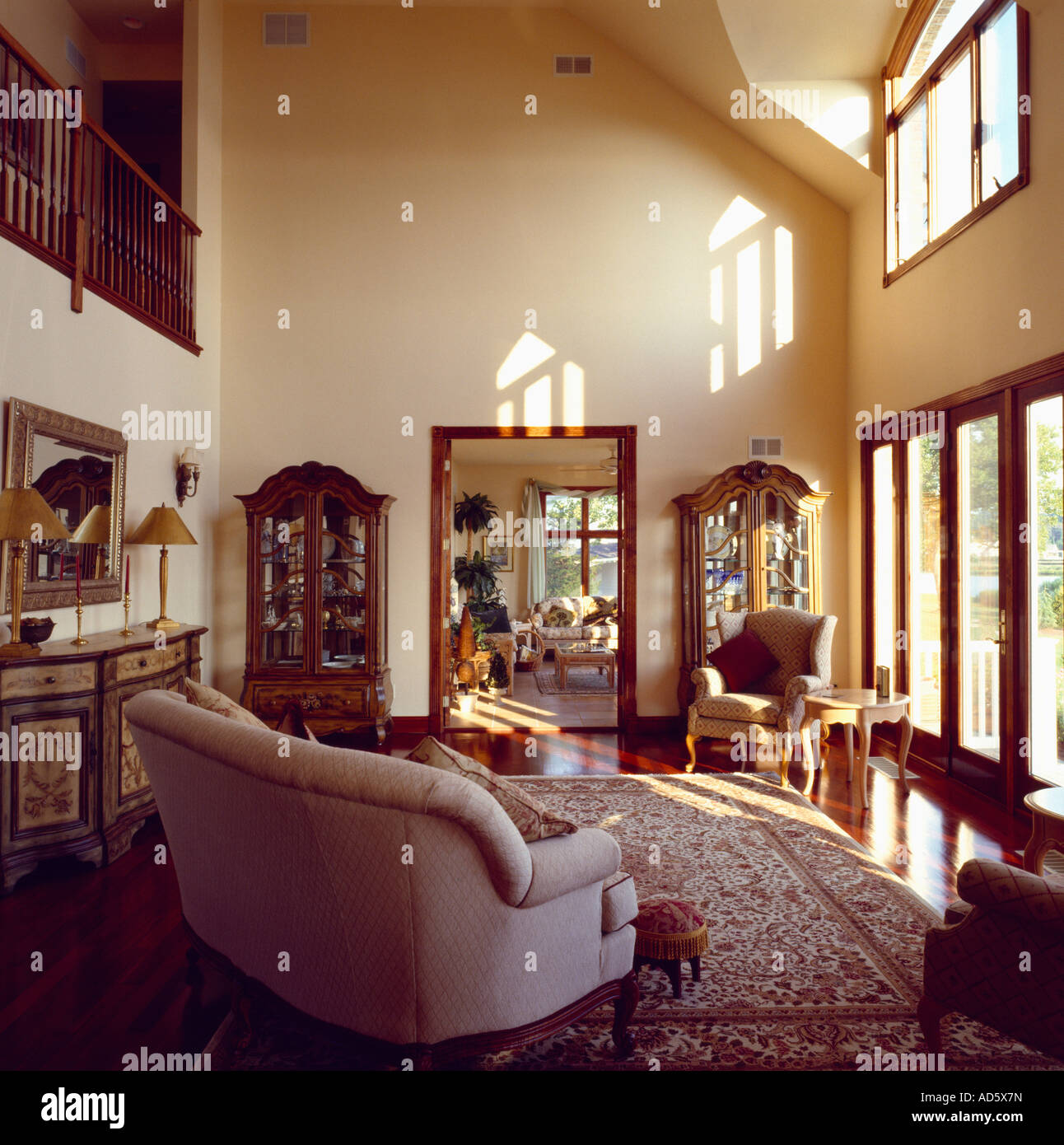 Traditional Furniture In Double Height Modern Living Room With Glass Patio  Doors And Cream Walls