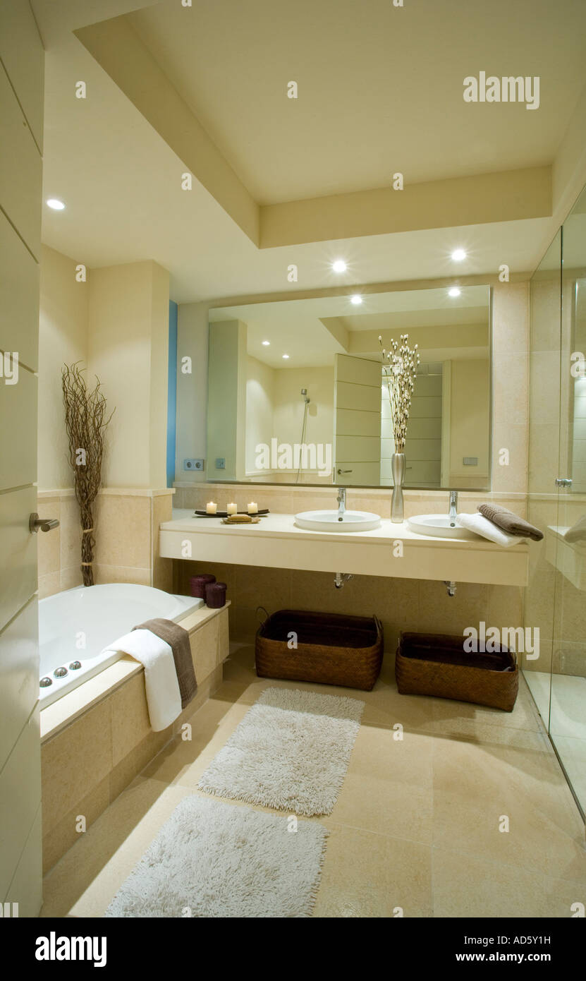 Cream bathmats on floor of modern neutral bathroom with large mirror above vanity unit with built in double basins - Stock Image