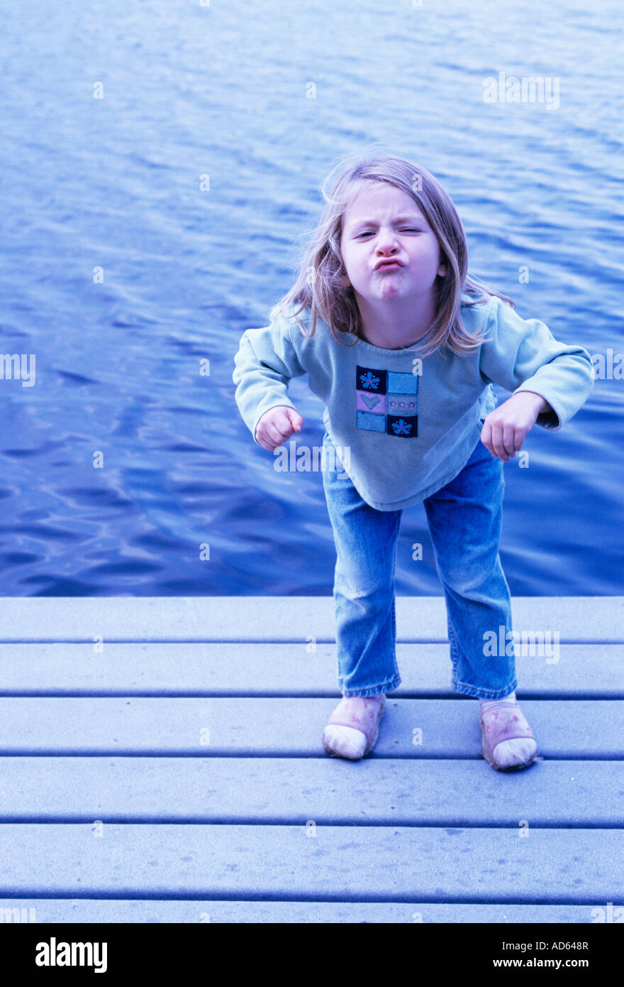 Young girl on dock making face - Stock Image
