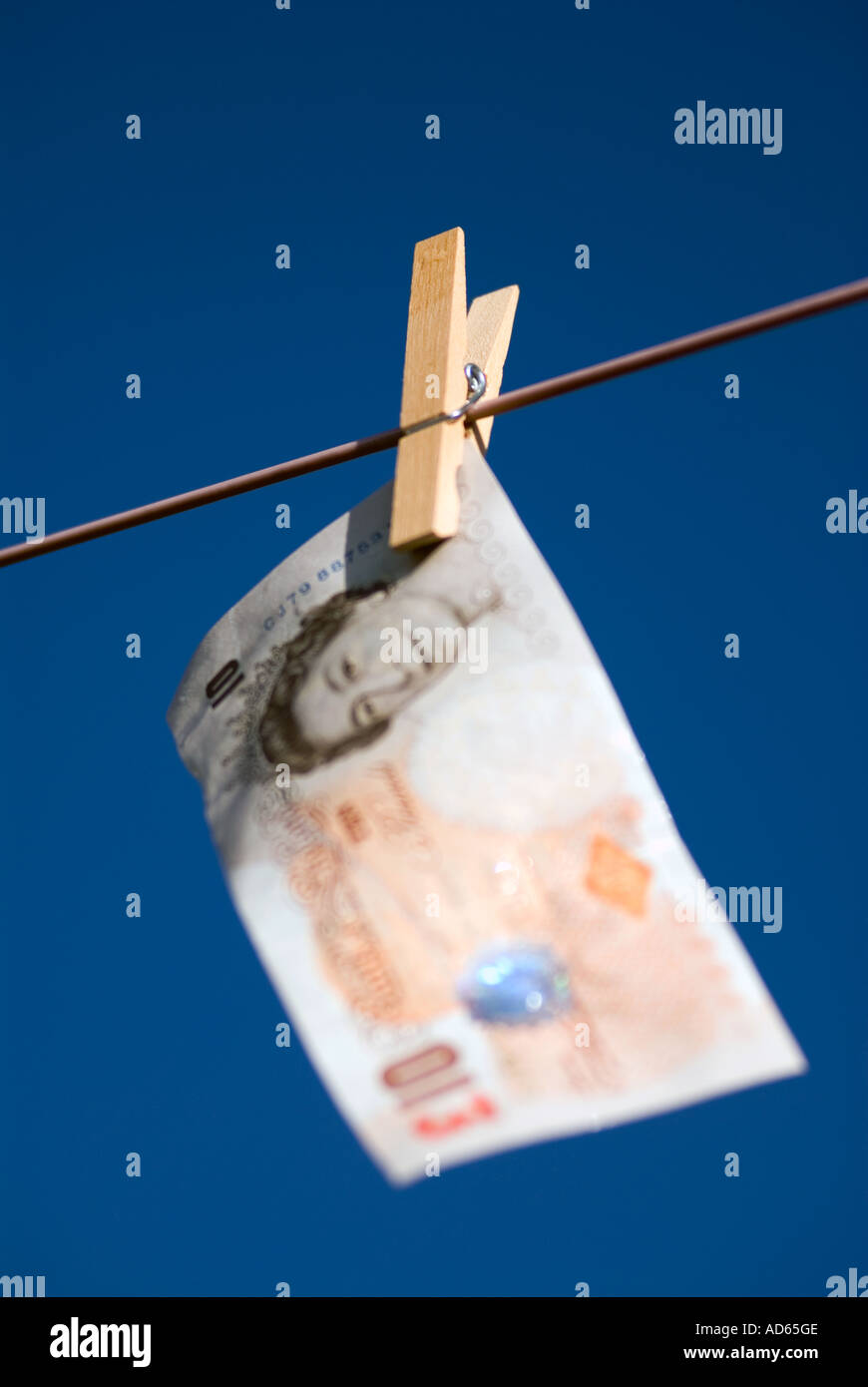 Concept Hanging money out to dry Ten pound note United Kingdon of Great Britain The peg is in focus The bank note Stock Photo