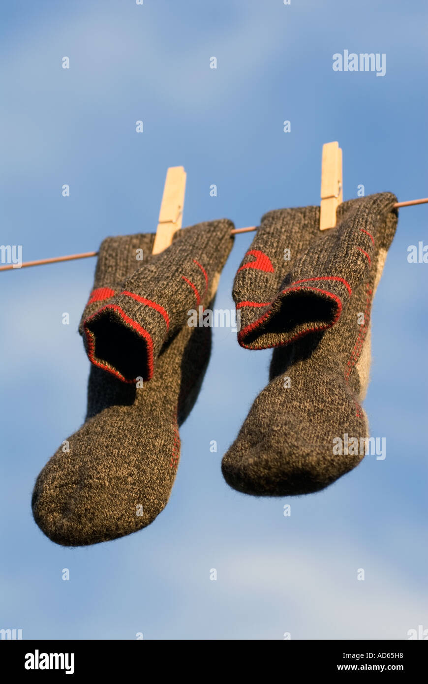 PICTURE CREDIT DOUG BLANE Concept A pair of clean grey gray and red wool walking socks hanging on a washing line to dry - Stock Image