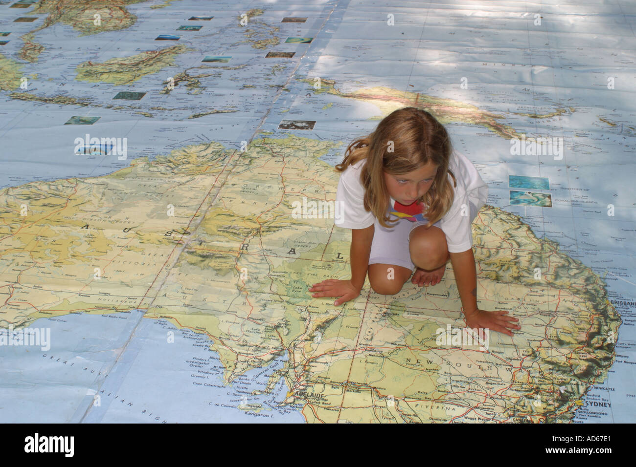 Young girl sitting on Australia part of a huge World map in an outdoor park - Stock Image