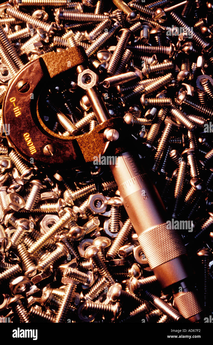 Micrometer measuring a nut on background of nut and bolts Stock Photo