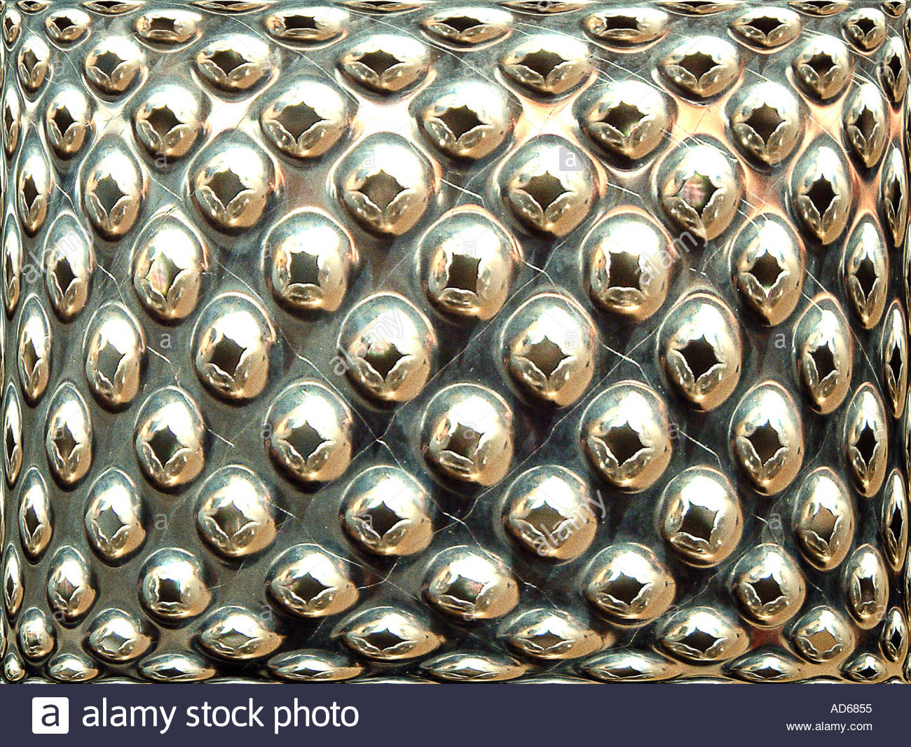 metallic grater bubbles bursting - Stock Image
