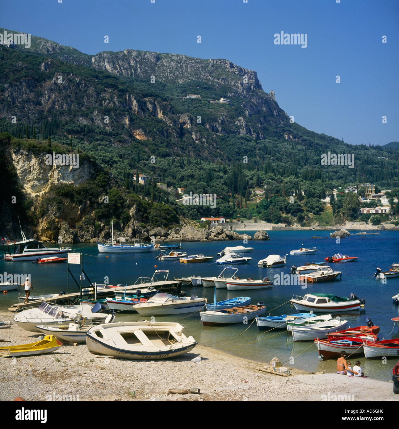 Alipa Harbour with numerous colourful boats moored in shallow waters and on pebbly beach at Paleokastritsa Corfu Greece - Stock Image