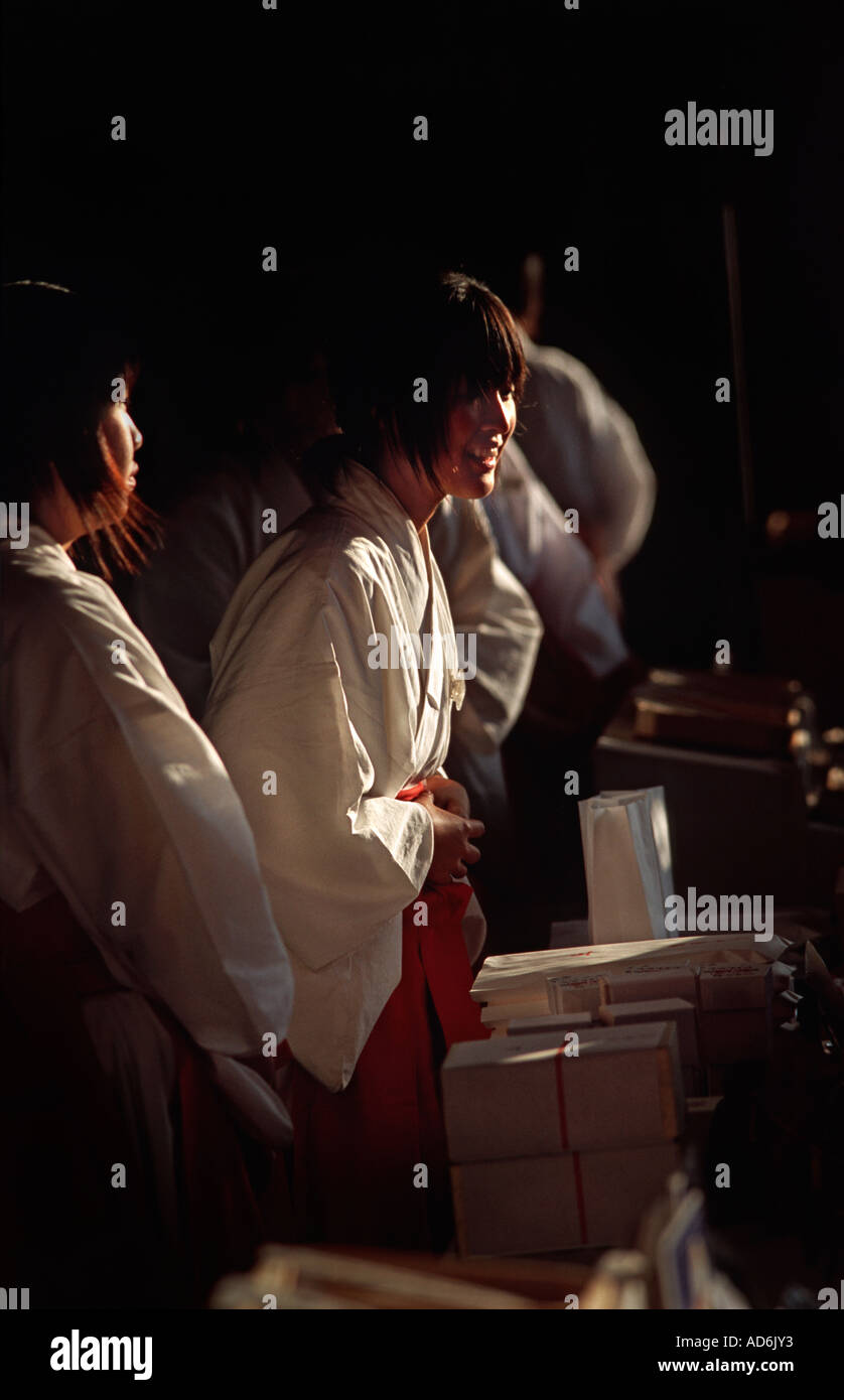 Volunteers at Kashihara shrine in white kimonos selling religious souvenirs New Year Japan - Stock Image