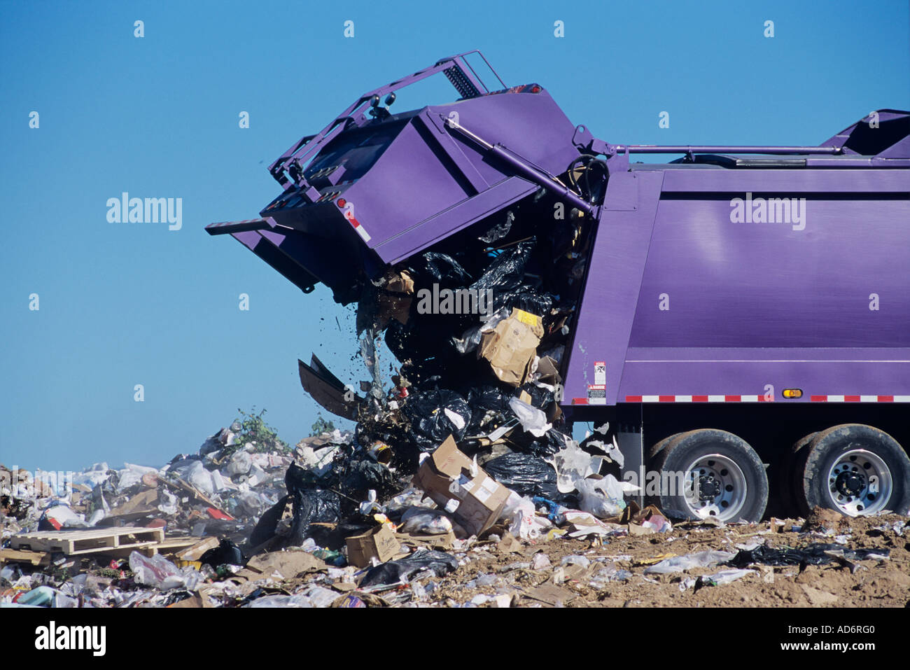 A large garbage truck dumps trash at a landfill - Stock Image