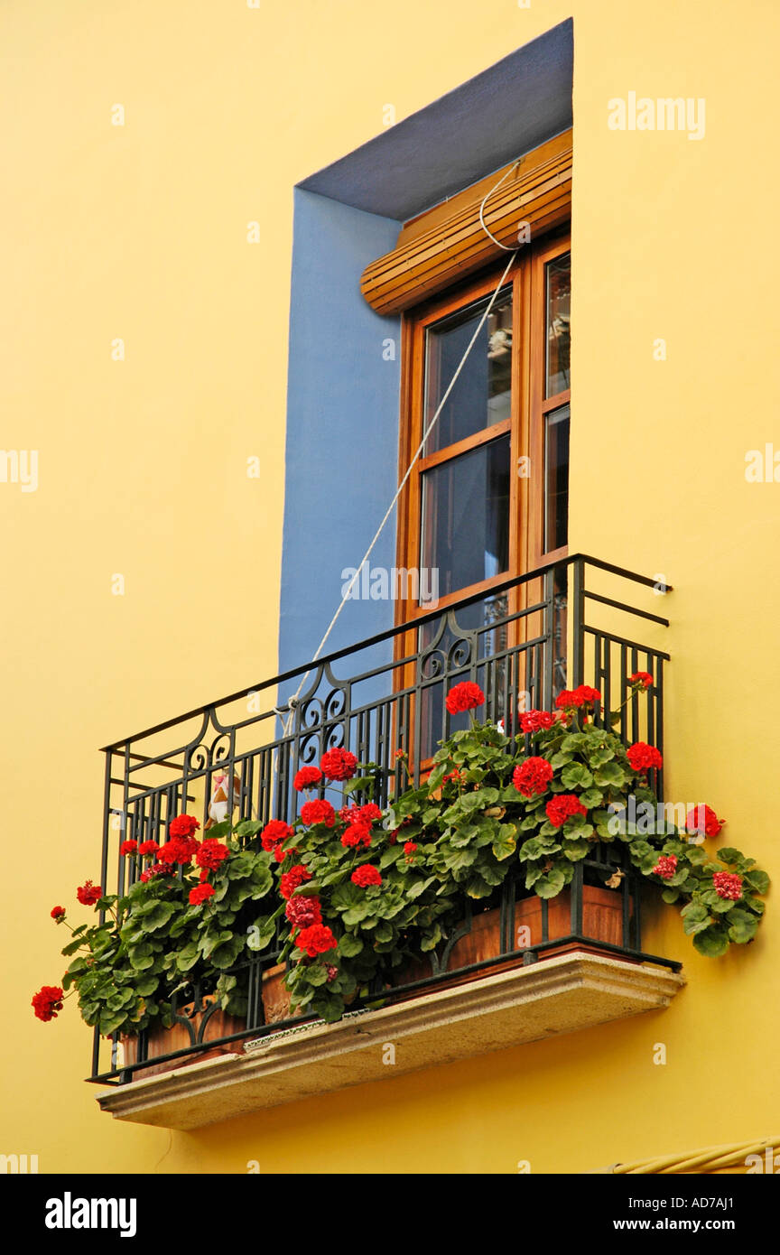 Small balcony decorated with red flowers in front of the window of a ...