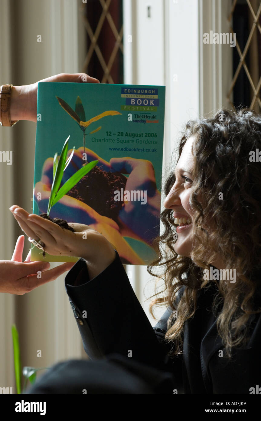 Young woman holding a growing plant in her palm, mimicking the image on the book behind. - Stock Image