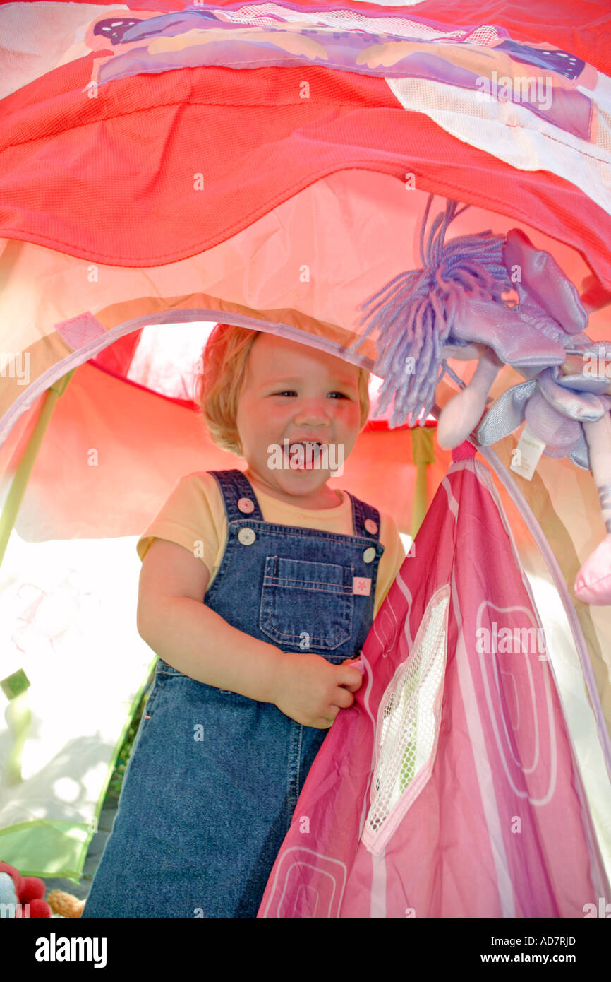 Toddler playing and laughing in pink play tent - Stock Image