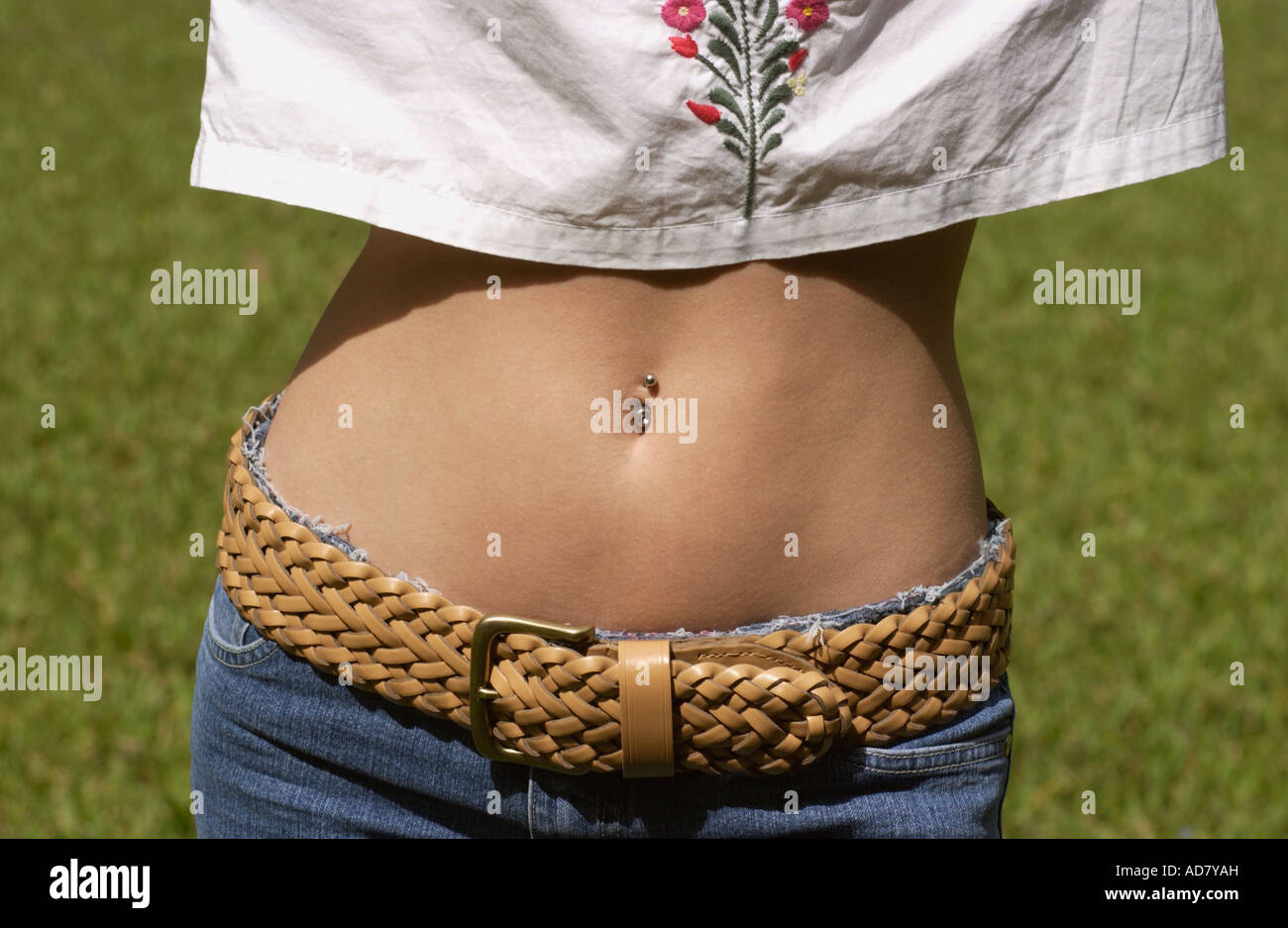 07ec9c51a6f92 Woman shows her bare midriff with a belly button ring while wearing a white  shirt and jeans