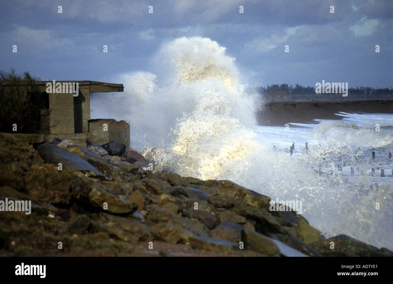 Waves crash against a Second World War pillbox, East Lane, Bawdsey Suffolk, UK. - Stock Image