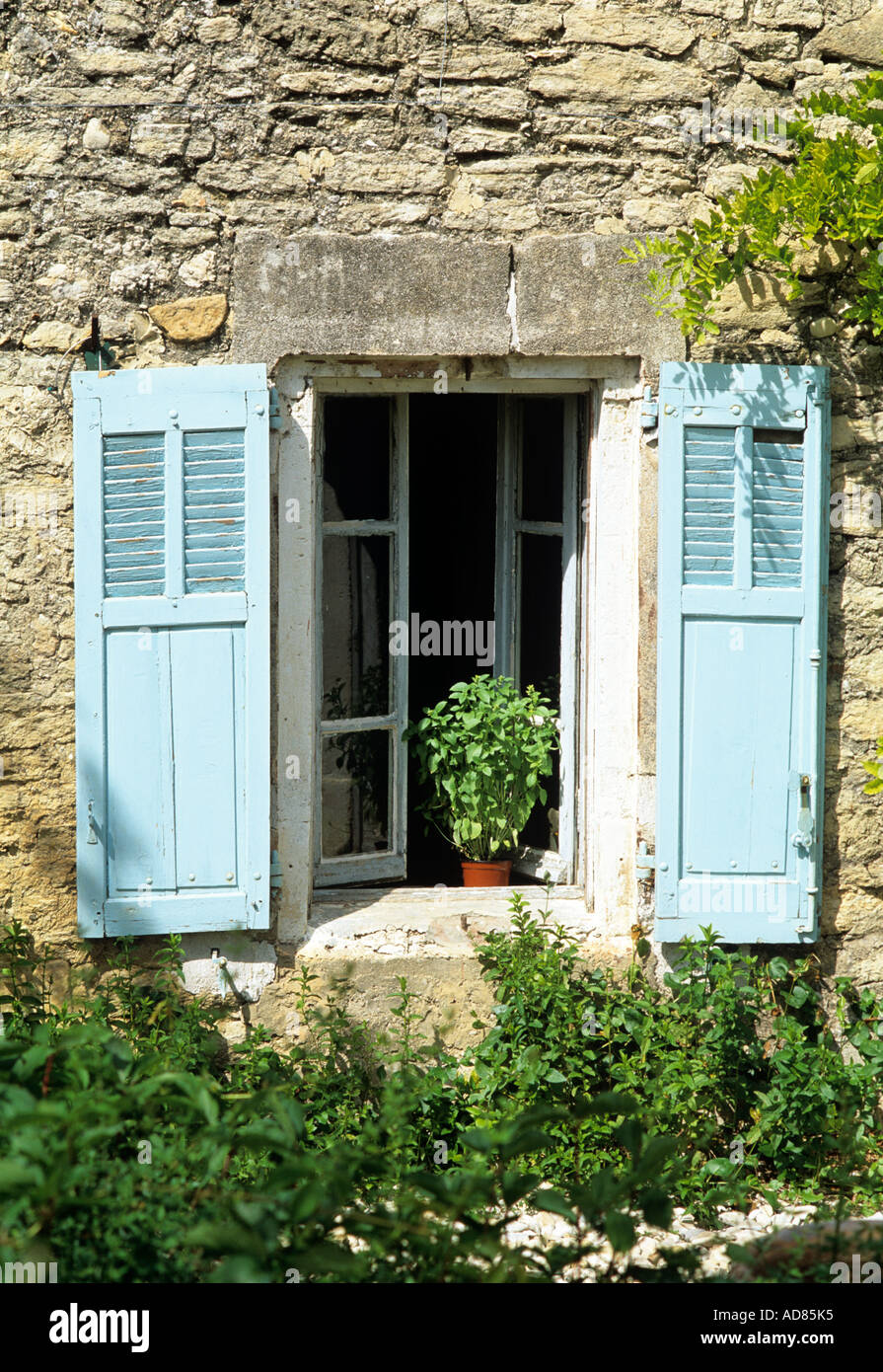 Blue shutters on the window of a traditional Provençal stone house, France - Stock Image