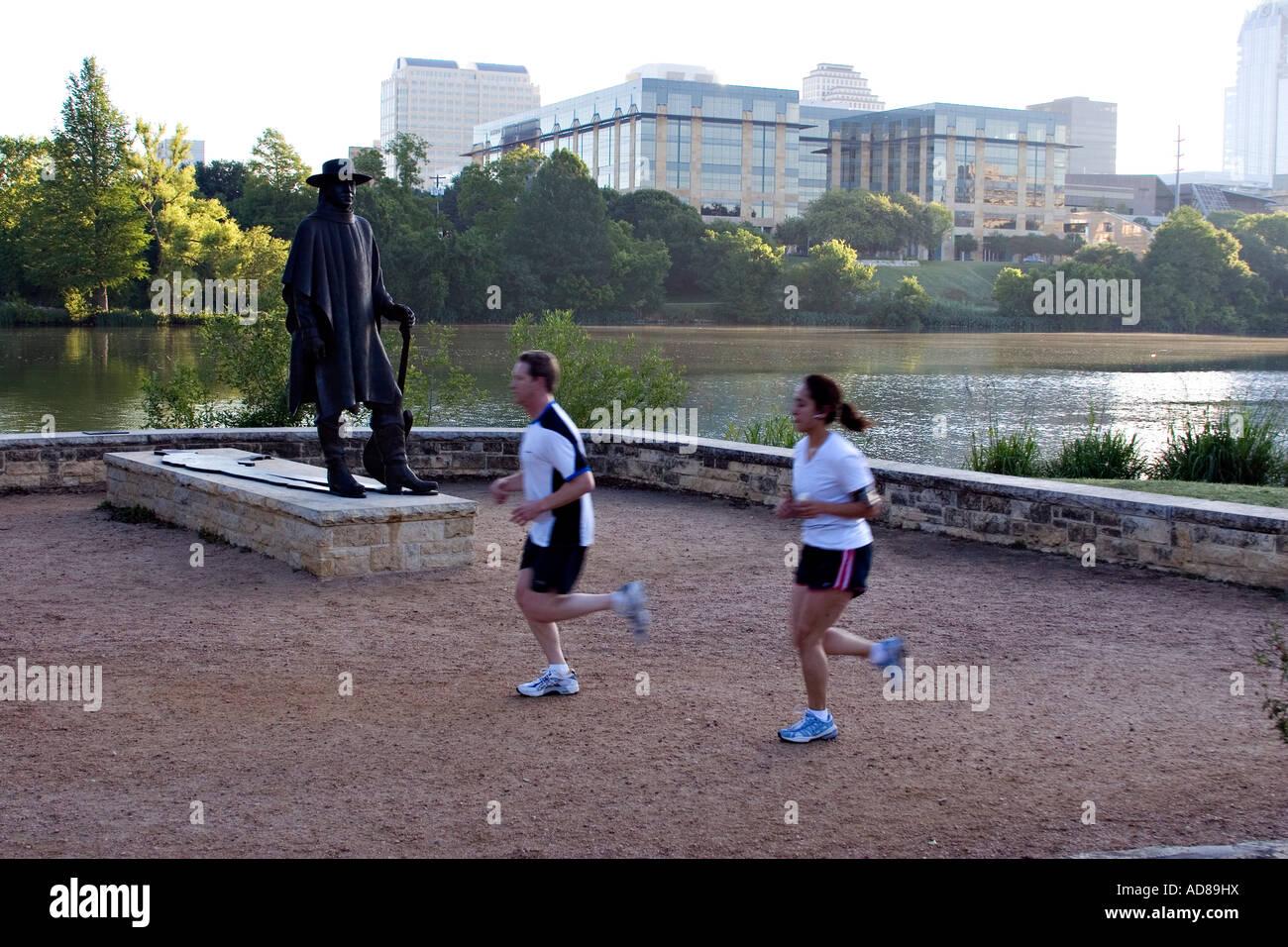 Joggers run past the Stevie Ray Vaughn memorial statue in Austin Texas - Stock Image