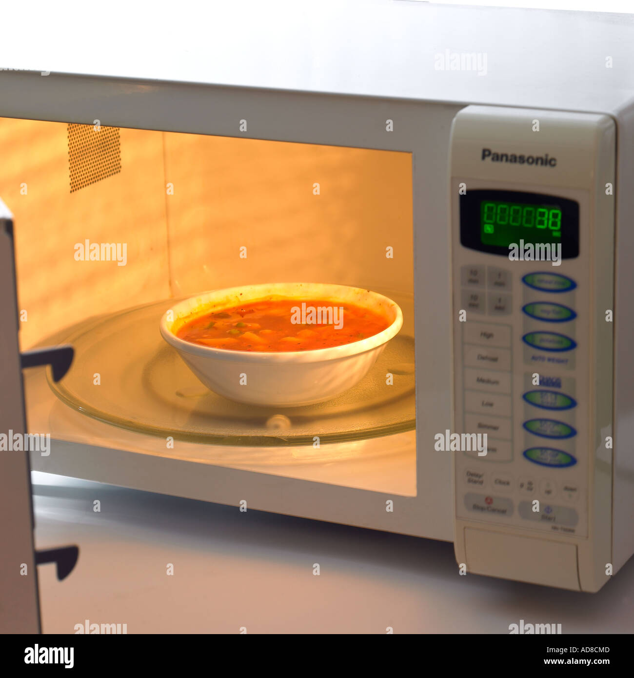 Bowl Of Carrot Or Vegetable Soup Reheated Inside Microwave, Door Open And  Splashed With Heated Soup