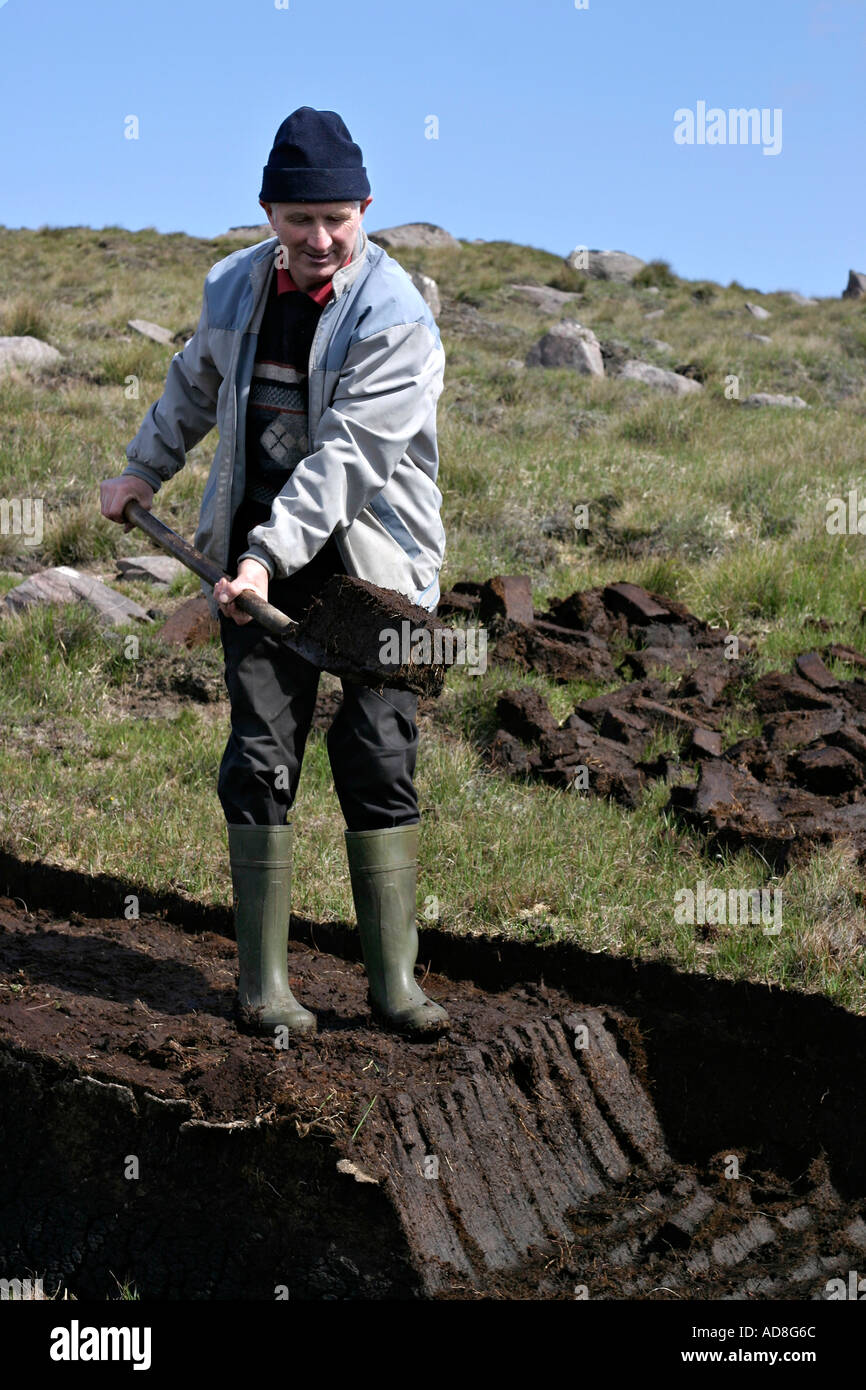Traditional peat digger Chris Gallagher working his family pot of sod using a traditional wood and iron peat spade - Stock Image