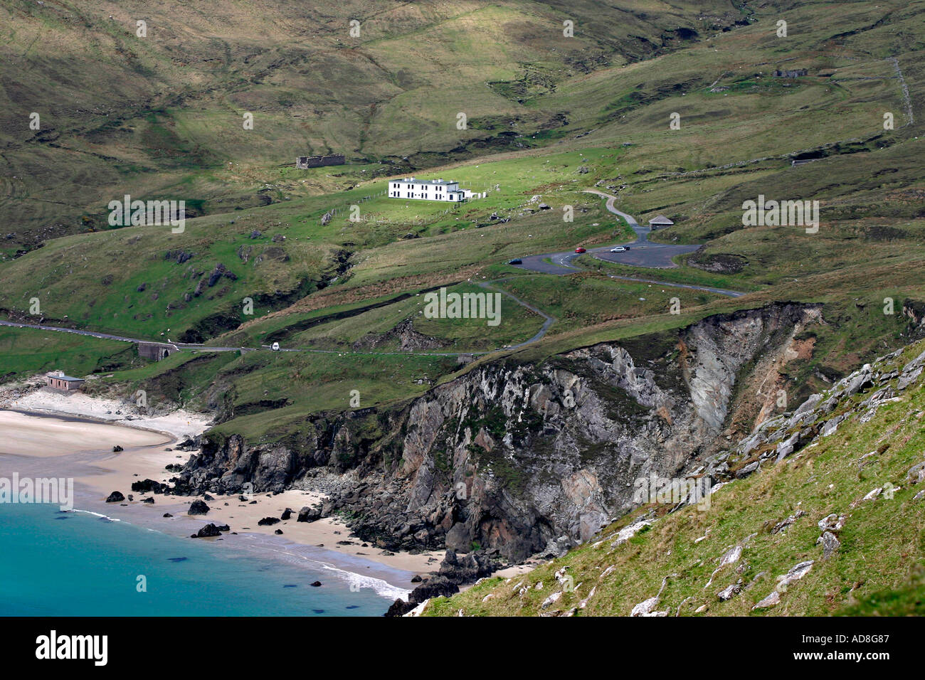 The house and beach at the end of the road on Achill. Turquoise water surrounds the beach and a sunbeam catches the white house - Stock Image