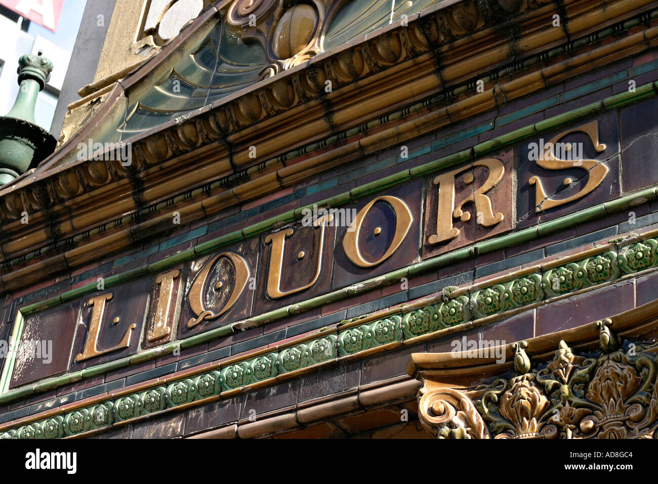 A detail of the ceramic tile work of the front facade of the famous Belfast landmark of Crown Liquor Saloon Bar: Liquors - Stock Image