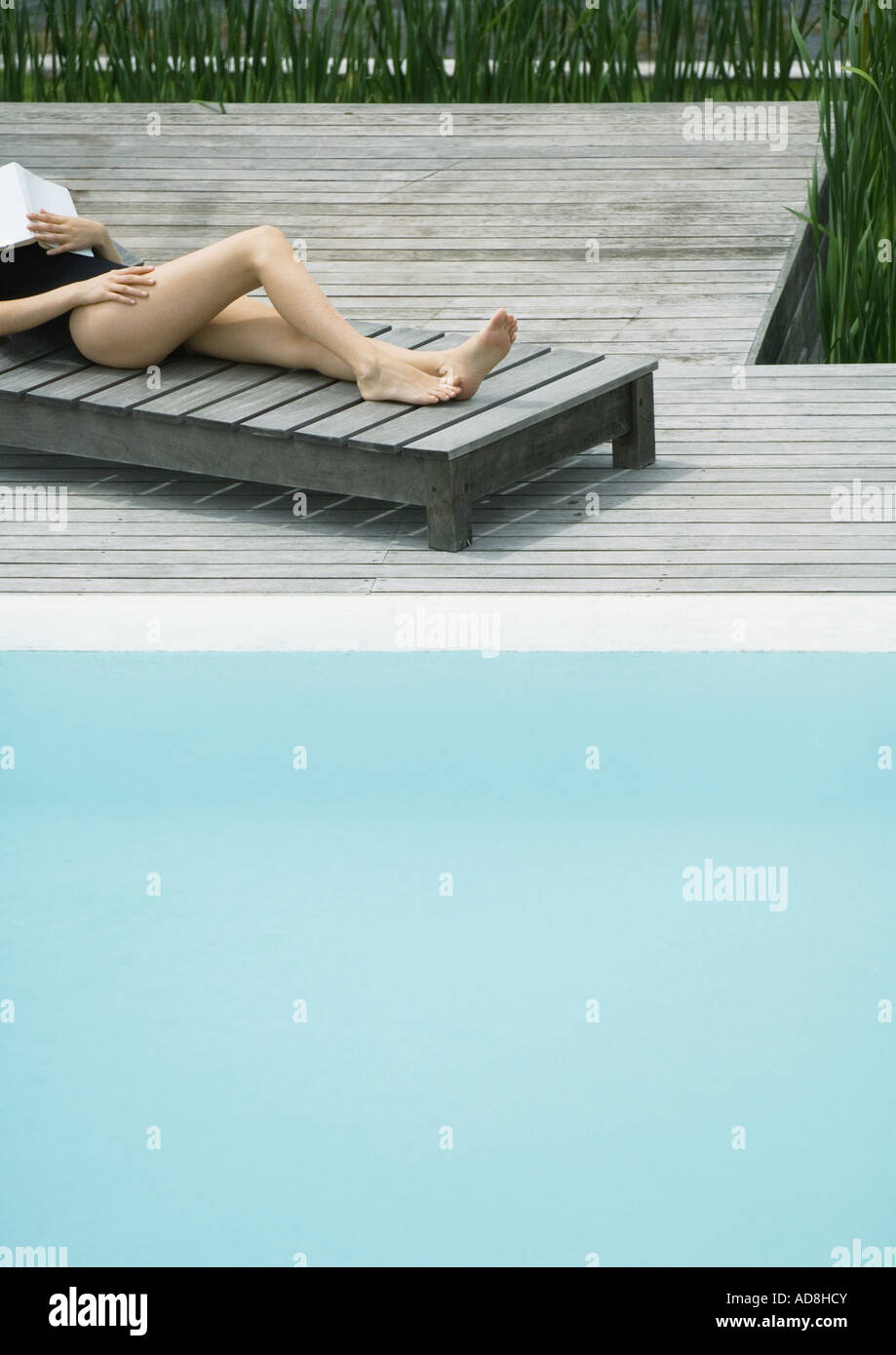 Woman reclining on lounge chair next to pool, sleeping with book on chest, cropped view - Stock Image