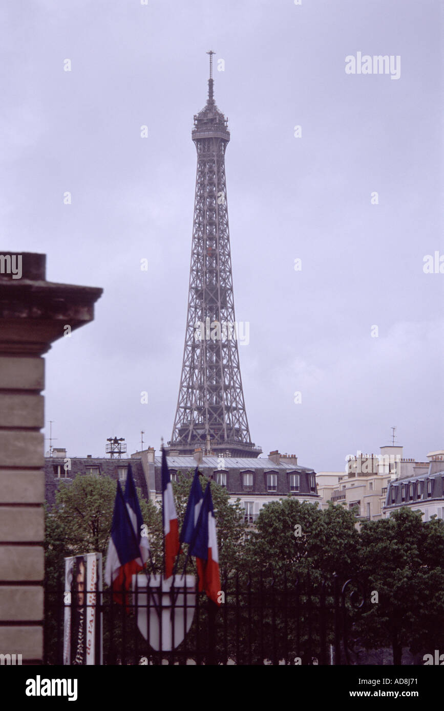 The Eiffel tower rises above Paris rooftops behind the French flag - Stock Image