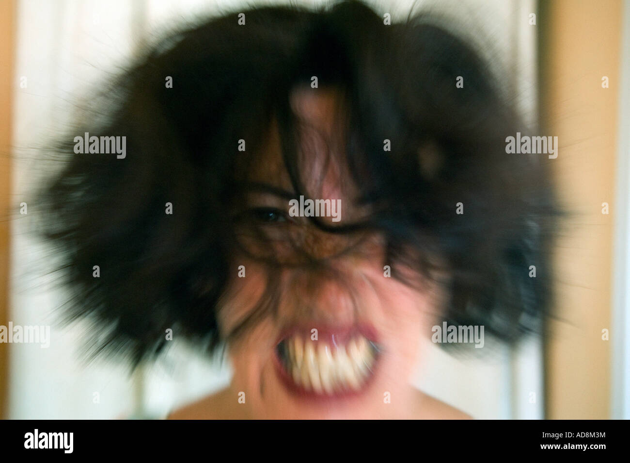 crazed woman with wild hair gritting her teeth - Stock Image
