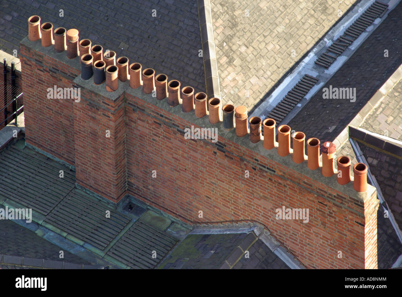 London looking down on long line of chimney pots on top of stack collecting together flues from multiple occupancy - Stock Image