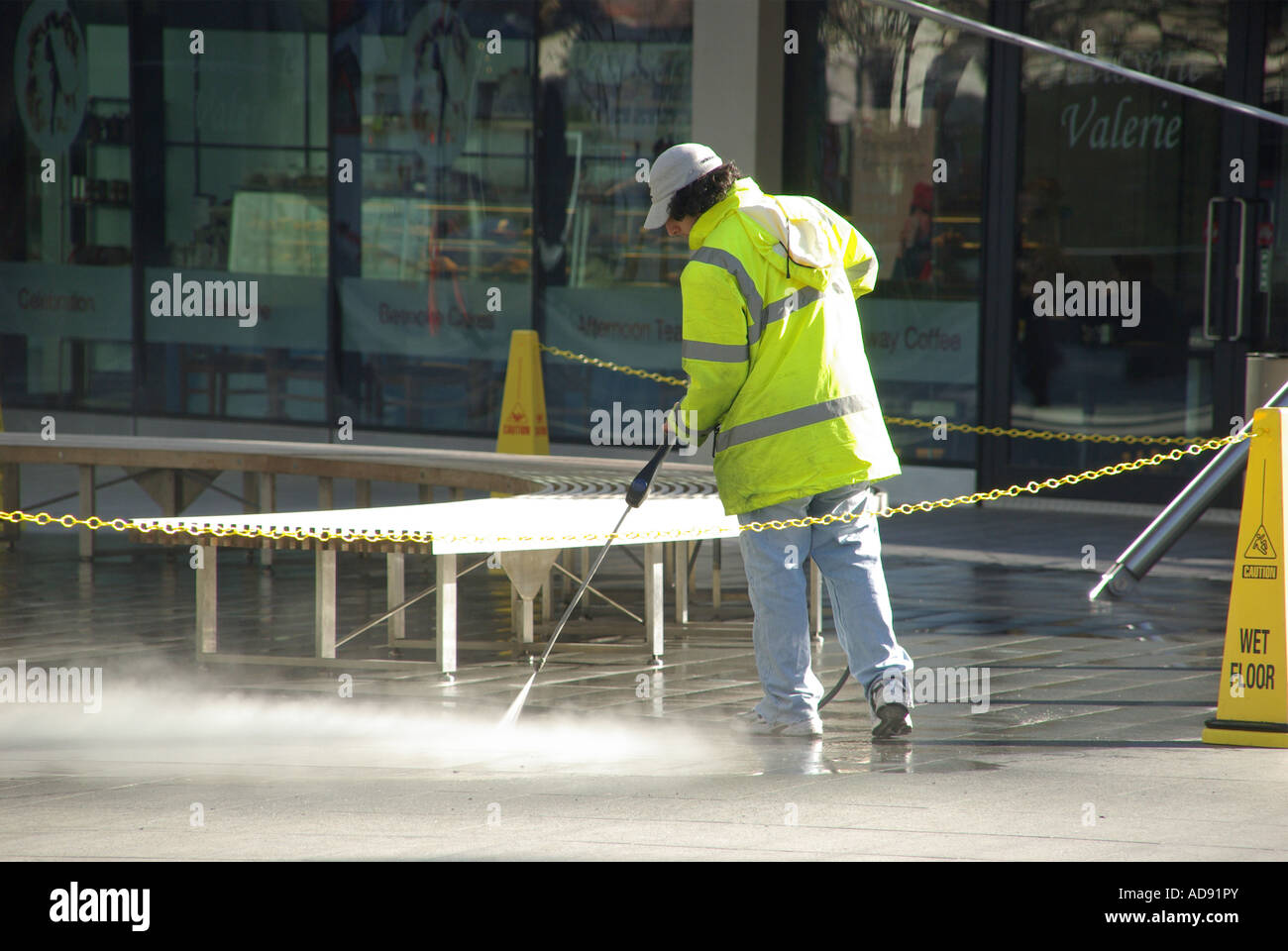 London high pressure water spray jet being used to clean paving of chewing gum & other grot by operator wearing - Stock Image