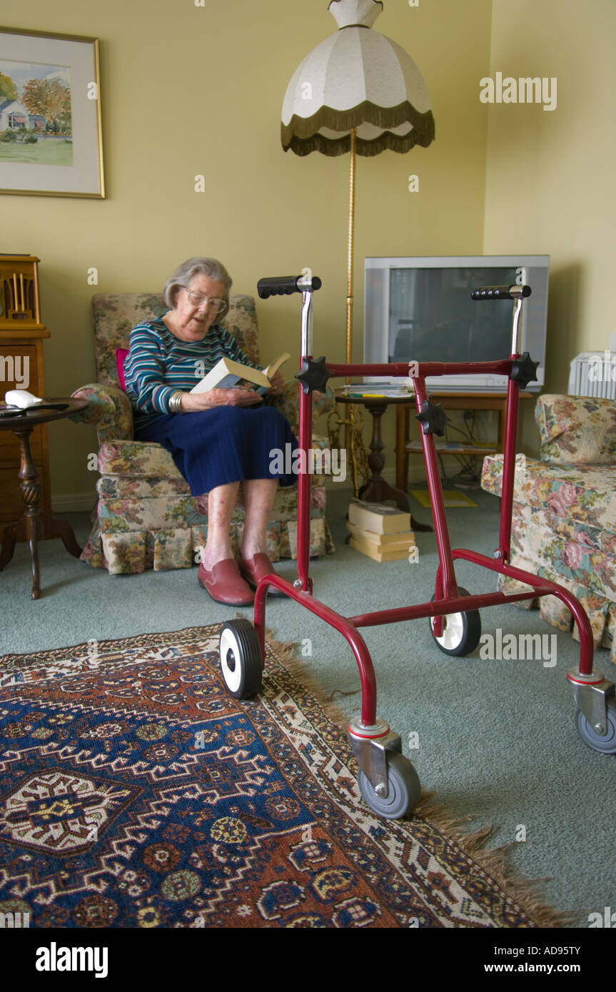 Elderly widow with walking frame reading in her retirement unit - Stock Image