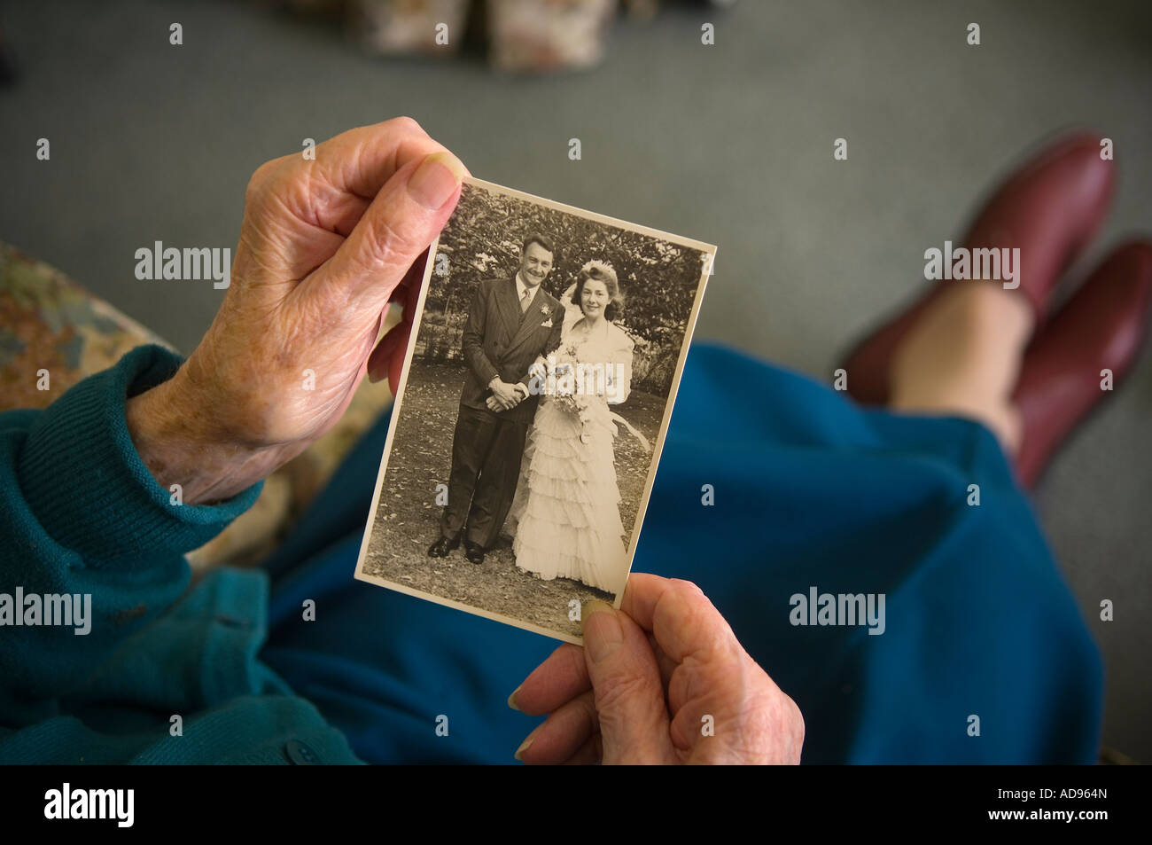Elderly widow looks at photograph of herself and husband on their wedding day - Stock Image