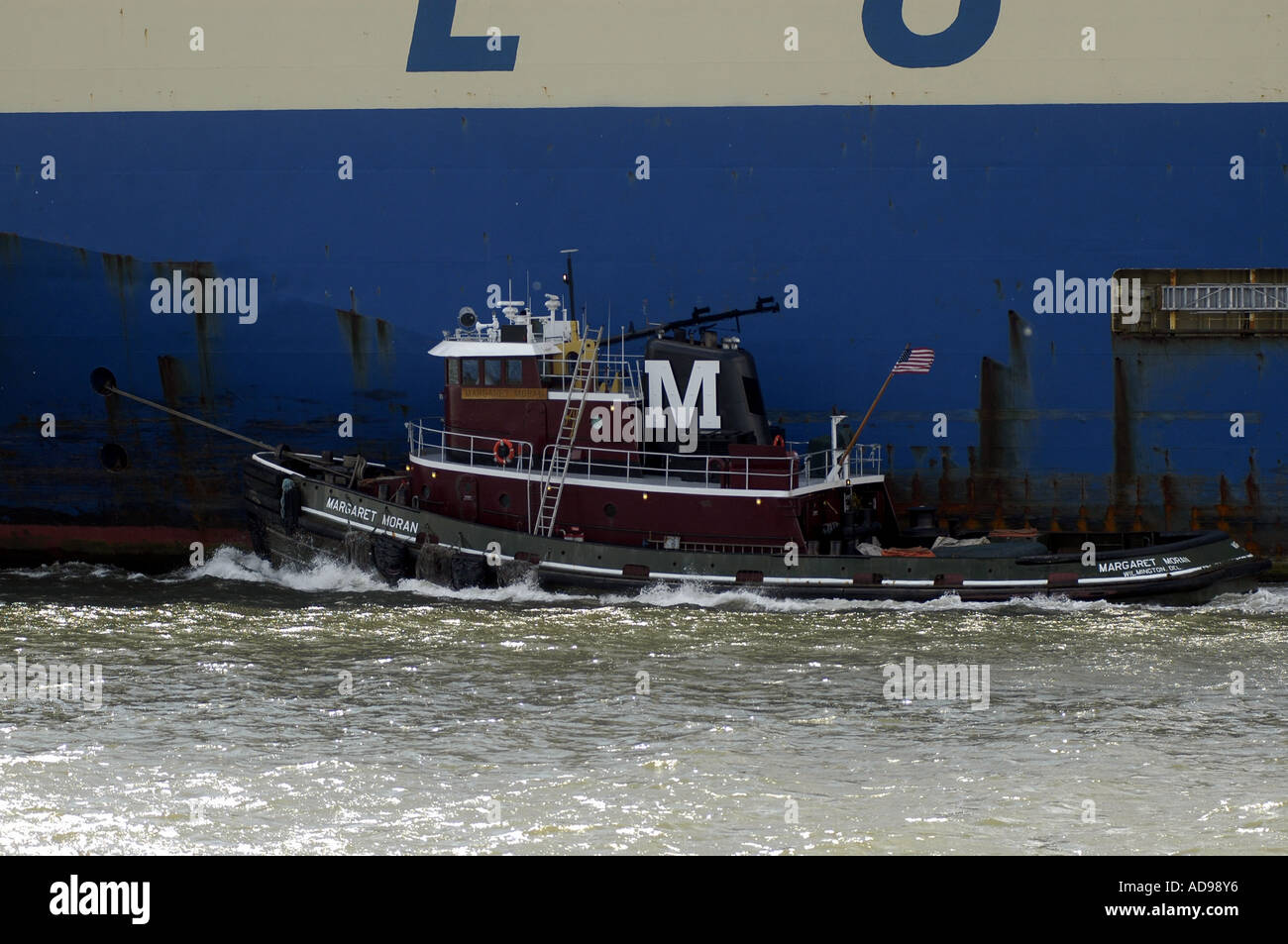 A tugboat guides the Hyundai 205, an automobile transport ship in New York Harbor - Stock Image