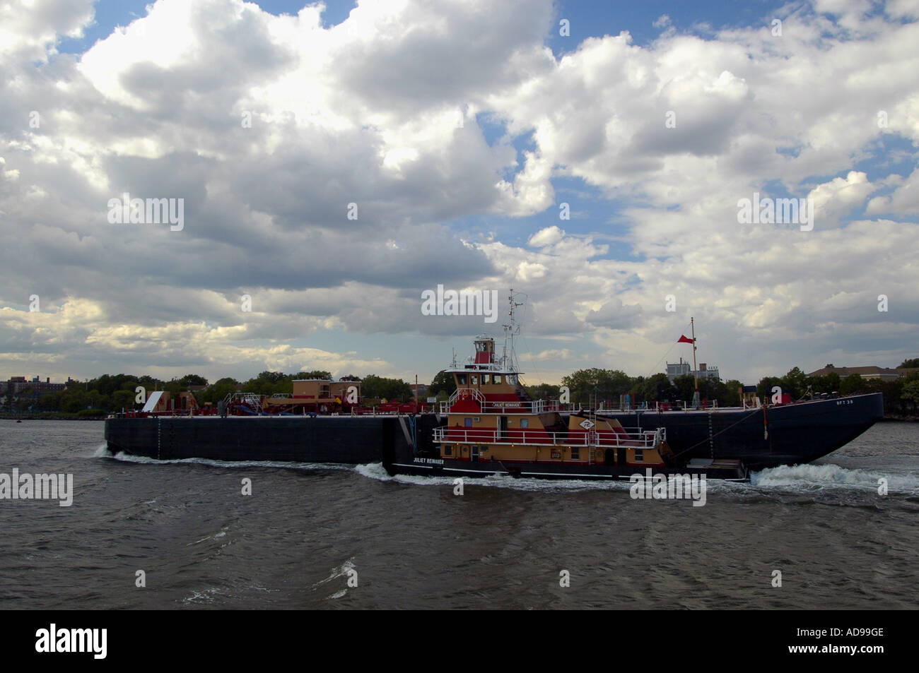 A tugboat hauls barges in NY Harbor - Stock Image