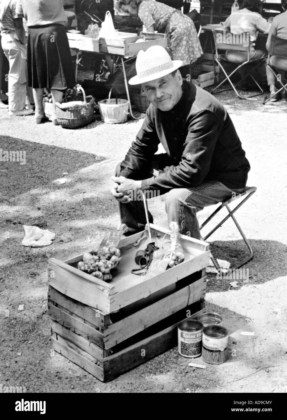 no MR street photography man trying to sell garlic at the market of Caussade in southern France - Stock Image