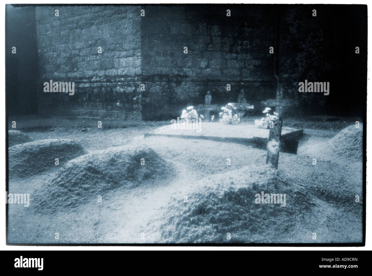 burial mounds beneath mural of a church in Brittany - Stock Image