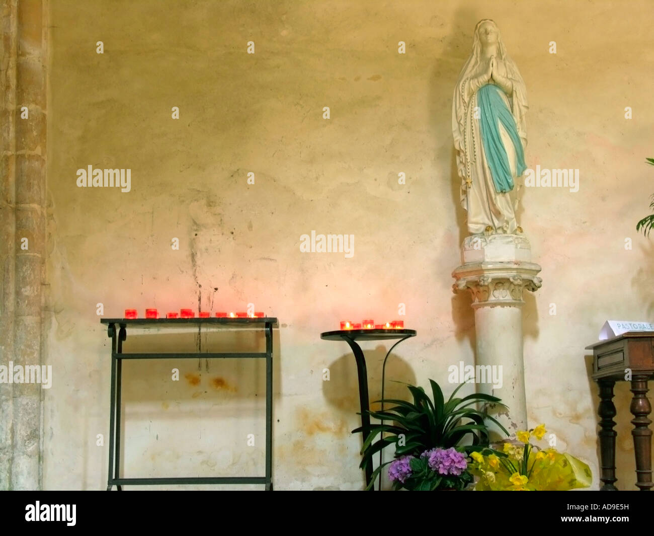 statue of the Blessed Virgin Mary with burning candles in a church ...