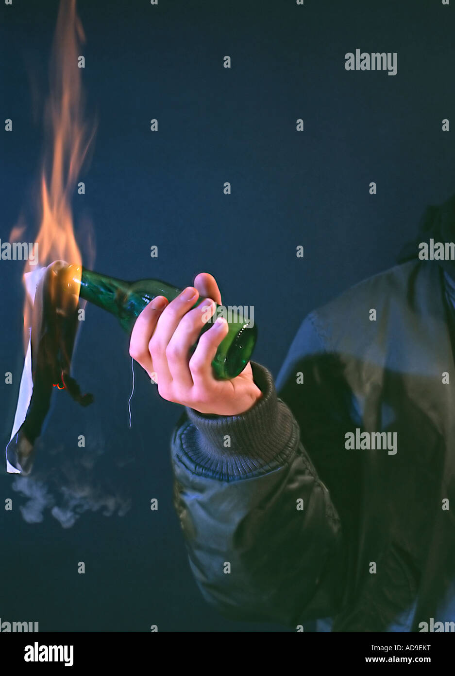 hand throwing a Molotwcoctail burning bottle radical person in black bomber jacket - Stock Image