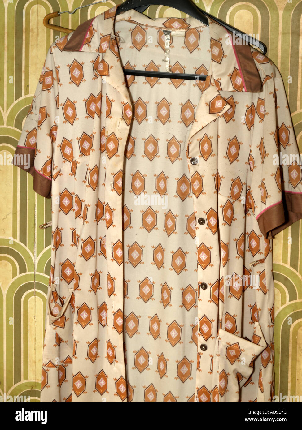 old smock hanging at wall with wallpaper from seventies - Stock Image
