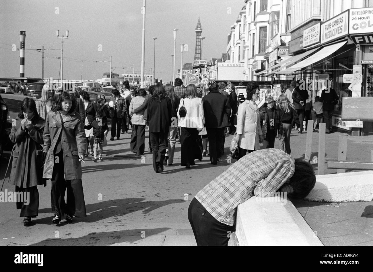 Depressed youth. Crowds walk up and down the  promenade,  Blackpool. The Golden Mile, Lancashire  England 1974 HOMER Stock Photo